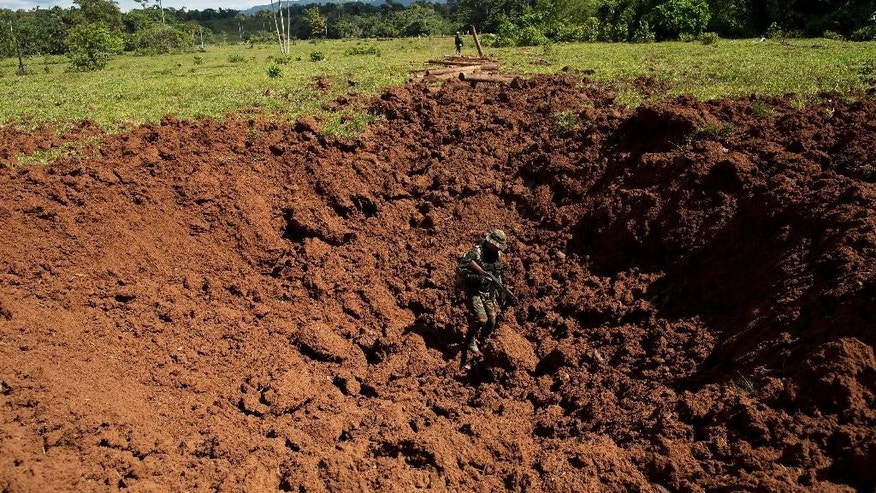 "In this July 28, 2015 photo, a Peruvian counternarcotics police officer stands in a crater blown into a clandestine airstrip used by cocaine traffickers in Ciudad Constitucion, Peru. Sonia Medina, the public prosecutor for illicit drugs, said in an interview that trafficking has gone ""from bad to worse"" on President Ollanda Humala's watch, along with narco-corruption in politics, the criminal justice system, the police and military. ""What we are doing in counternarcotics is completely distorted, incoherent and inert."" (AP Photo/Rodrigo Abd)"