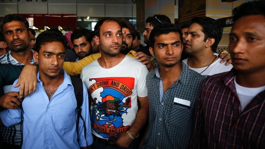 Indian sailor Sushil Kapoor, second left, with his other freed colleagues stand at the Indira Gandhi International Airport in New Delhi, India, Wednesday, Oct. 14, 2015 Officials say nine Indian sailors held in Iran for two years on charges of smuggling oil have been freed. (AP Photo/Manish Swarup)