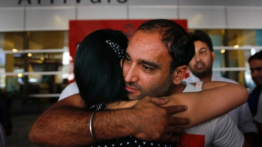 Indian sailor Sushil Kapoor hugs a relative on his arrival at the Indira Gandhi International Airport in New Delhi, India, Wednesday, Oct. 14, 2015 Officials say nine Indian sailors held in Iran for two years on charges of smuggling oil have been freed. (AP Photo/Manish Swarup)