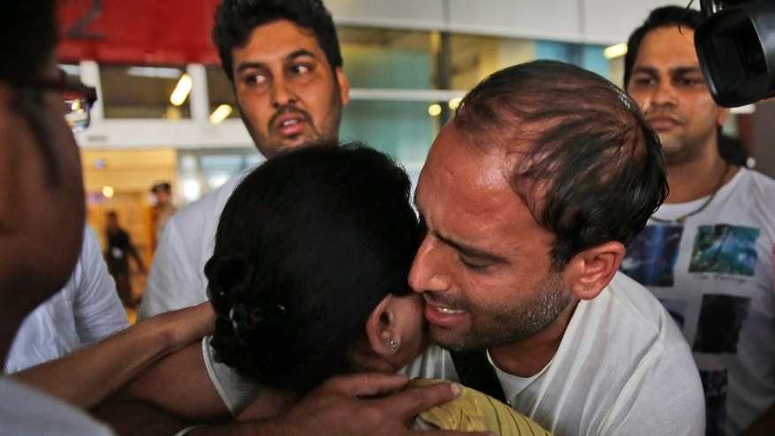 Indian sailor Sushil Kapoor hugs his mother on his arrival at the Indira Gandhi International Airport in New Delhi, India, Wednesday, Oct. 14, 2015 Officials say nine Indian sailors held in Iran for two years on charges of smuggling oil have been freed. (AP Photo/Manish Swarup)
