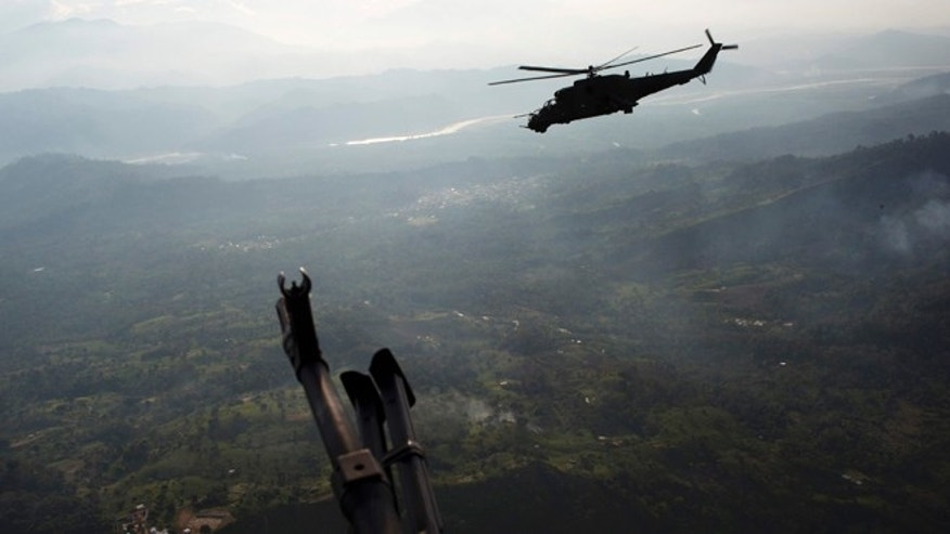 In this Sept. 19, 2014, file photo, a military attack helicopter flies over Pichari, Peru in the Apurimac, Ene and Mantaro river valley, or VRAEM. It is the world's No. 1 coca-growing region. Roughly half of Perus cocaine exports have been ferried eastward, police say, since the rugged Andean nation became the worlds leading producer of the drug in 2012. (AP Photo/Rodrigo Abd, File)