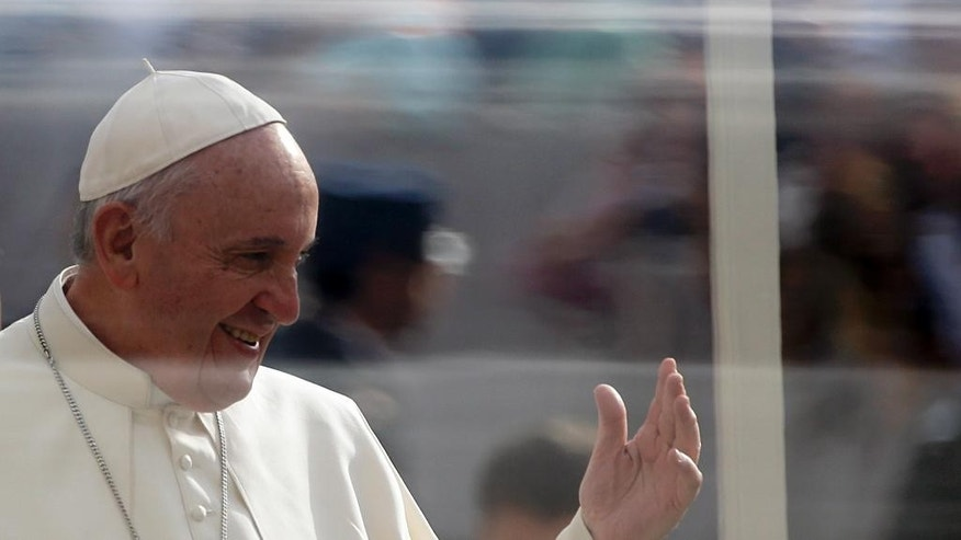 Pope Francis delivers a blessing as he arrives in St. Peter's Square for the weekly general audience, at the Vatican, Wednesday, Oct. 14, 2015. (AP Photo/Gregorio Borgia)