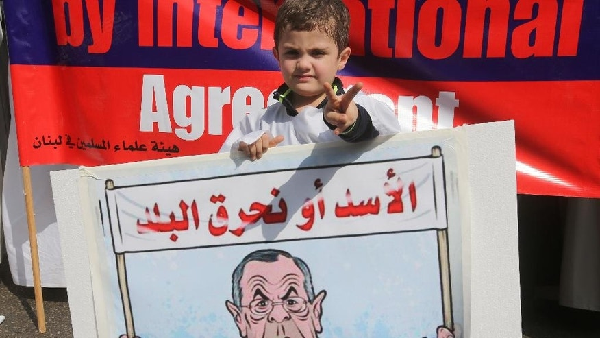 """A Lebanese boy holds a placard depicting Russian foreign minister Sergey Lavrov and Arabic that reads, """"Assad or we burn the country,"""" during a sit-in in front the Russian embassy, in Beirut, Lebanon, Wednesday, Oct. 14, 2015. Moscow, which began its airstrikes in Syria on Sept. 30, said it is targeting Islamic State and other militant groups. But it has also struck positions of rebel groups supported by the West and other regional players. (AP Photo/Hussein Malla)"""