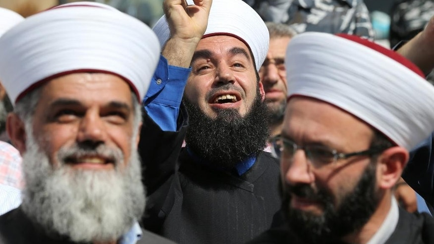 A Lebanese Sunni cleric, center, smiles as he gestures to a Russian security man, not seen, on the top of the Russian embassy building, to stop taking pictures, during a sit-in against Russian intervention in Syria, in front the Russian embassy, in Beirut, Lebanon, Wednesday, Oct. 14, 2015. Moscow, which began its airstrikes in Syria on Sept. 30, said it is targeting Islamic State and other militant groups. But it has also struck positions of rebel groups supported by the West and other regional players. (AP Photo/Hussein Malla)
