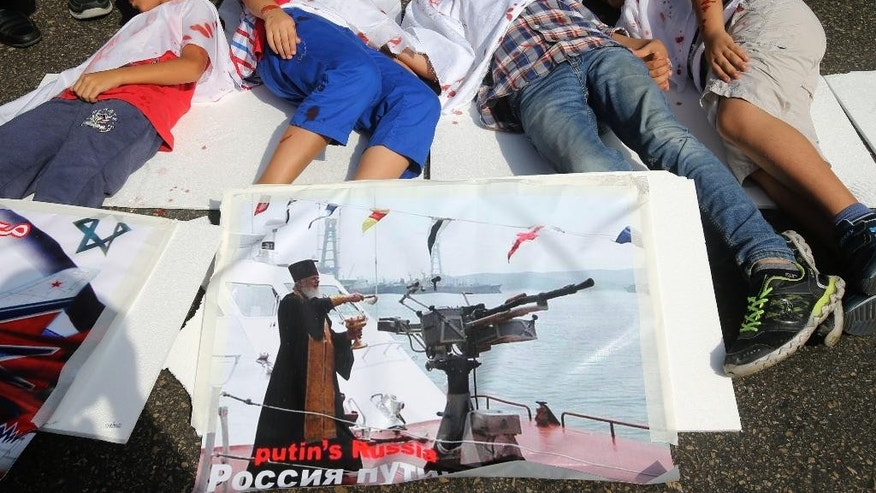Lebanese boys depict Syrian boys who were killed by Russian airstrikes, during a sit-in in front the Russian embassy, in Beirut, Lebanon, Wednesday, Oct. 14, 2015. Moscow, which began its airstrikes in Syria on Sept. 30, said it is targeting Islamic State and other militant groups. But it has also struck positions of rebel groups supported by the West and other regional players. (AP Photo/Hussein Malla)