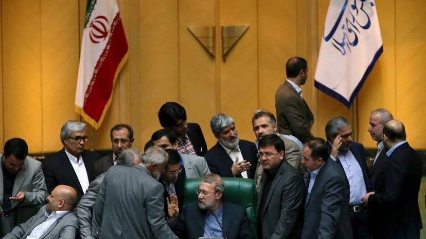 In this photo taken on Sunday, Oct. 11, 2015, Iran's parliament speaker Ali Larijani, center, speaks with lawmakers in an open session of parliament while discussing a bill on Iran's nuclear deal with world powers, in Tehran, Iran. Iran's parliament voted Tuesday to support implementing a landmark nuclear deal struck with world powers despite hard-line attempts to derail the bill, suggesting the historic accord will be carried out. (AP Photo/Ebrahim Noroozi)