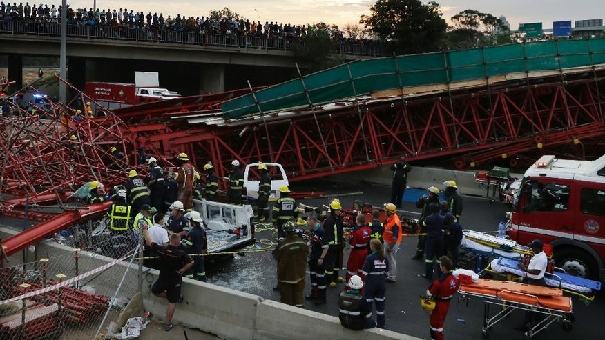 Emergency service workers and paramedics help an injured man from a vehicle, which was partly crushed beneath scaffolding after a temporary bridge collapse in Johannesburg, South Africa, Wednesday, Oct. 14, 2015.  A temporary bridge that was part of a construction project collapsed onto one of South Africa's busiest highways on Wednesday.  (AP Photo/Themba Hadebe)