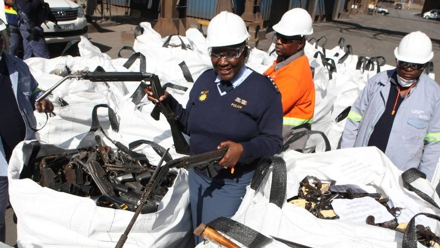 In this photo taken Thursday, July 9, 2015 national police commissioner Riah Phiyega inspects confiscated weapons prior to  smelting at a metal processing plant in Vereeniging, South Africa. Phiyega will remain on suspension with full pay until the board of inquiry into her fitness to hold office has completed its work, the presidency said Wednesday, Oct. 14 2015.(AP Photo/Denis Farrell)
