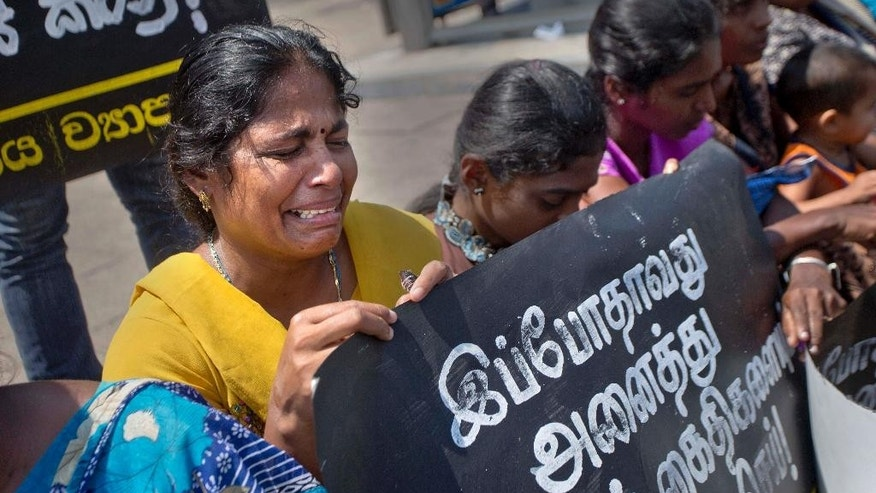 "A family member of an ethnic Tamil detainee cries during a silent protest in Colombo, Sri Lanka, Wednesday, Oct. 14, 2015. Relatives and civil rights activists are demanding the Sri Lankan government to release hundreds of minority ethnic Tamils detained without charges for years on suspicion of links to the now-defeated Tamil Tiger rebels. Placard reads ""Release all political prisoners now."" (AP Photo/Eranga Jayawardena)"