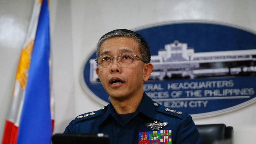 Col. Restituto Padilla, spokesman of the Armed Forces of the Philippines, reads the military's reaction to the video purportedly showing for the first time two Canadians, a Norwegian and a Filipino woman who were abducted last month from a southern Philippines resort, demanding that government forces stop artillery fire and assaults, following a news conference Wednesday, Oct. 14, 2015, at Camp Aguinaldo in suburban Quezon city, northeast of Manila, Philippines. Authorities were trying to verify the authenticity of the video, and the Philippine military said that they would reject any demands from the militants. (AP Photo/Bullit Marquez)