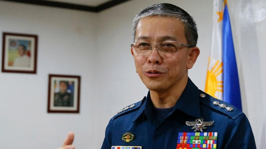 Col. Restituto Padilla, spokesman of the Armed Forces of the Philippines, gestures after reading the military's reaction to the video purportedly showing for the first time two Canadians, a Norwegian and a Filipino woman who were abducted last month from a southern Philippines resort, demanding that government forces stop artillery fire and assaults, following a news conference Wednesday, Oct. 14, 2015, at Camp Aguinaldo in suburban Quezon city, northeast of Manila, Philippines. Authorities were trying to verify the authenticity of the video, and the Philippine military said that they would reject any demands from the militants. (AP Photo/Bullit Marquez)