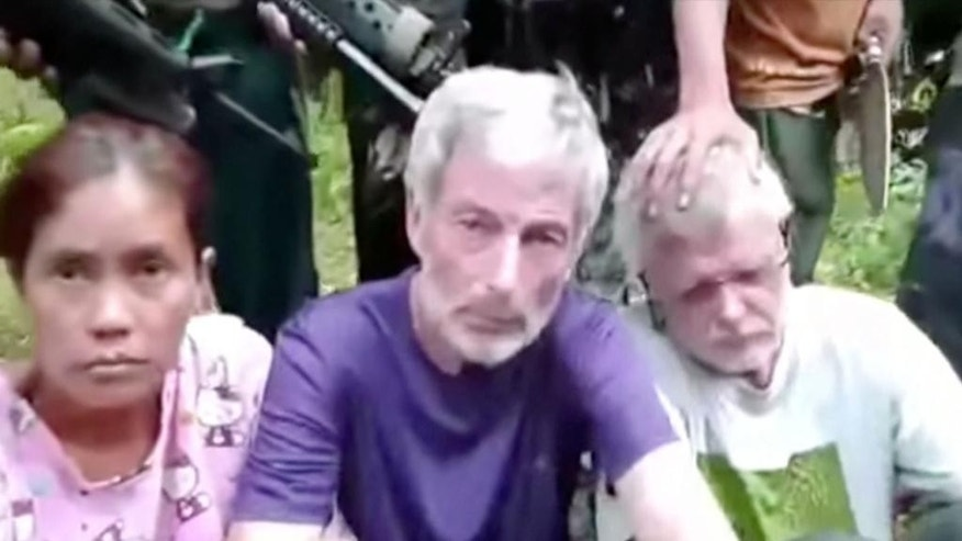 This frame grab from militant video purportedly shows armed militants surrounding two Canadians, a Norwegian and a Filipino woman abducted last month in the Philippines. The Philippine army said on Wednesday, Oct. 14, 2015, that authorities were trying to verify the authenticity of the video, adding that the military would reject any demands from the militants. (Militant Video via AP)