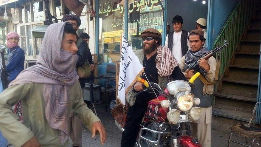 In this Sept. 29, 2015, file photo, a Taliban fighter sits on his motorcycle adorned with a Taliban flag in a street in Kunduz, Afghanistan. Within hours of seizing the northern city of Kunduz in September, Taliban fighters went door-to-door, hunting down not only those accused of working with security forces, but women's rights advocates and journalists. (AP Photo, File)