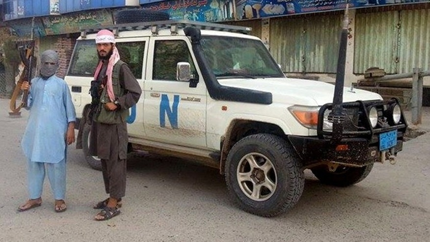 FILE - In this Sept. 29, 2015 file photo, Taliban fighters pose for a photo next to a UN vehicle they plundered in Kunduz, Afghanistan. (AP Photo/File)