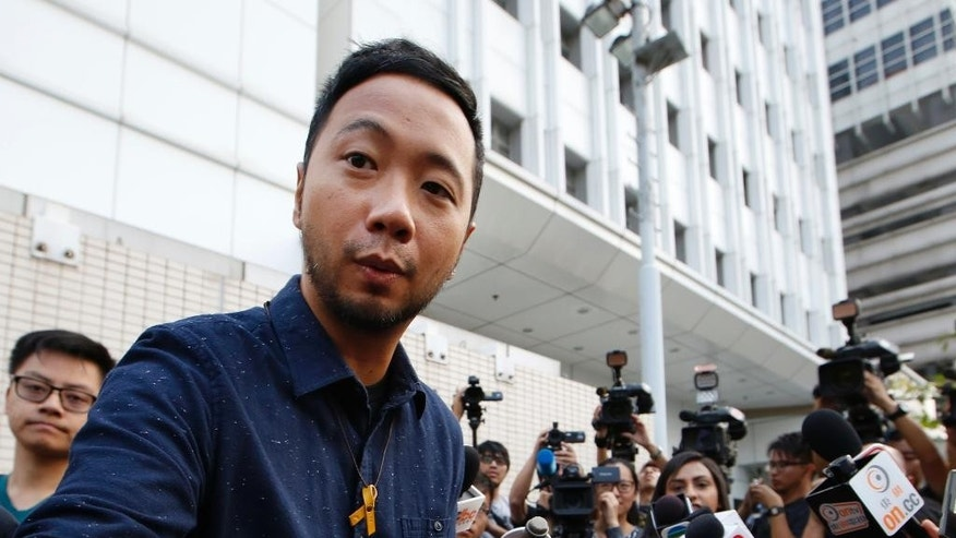 The activist, Ken Tsang, right, reports to a police station in Hong Kong, Thursday, Oct. 15, 2015. Hong Kong police on Thursday charged seven officers with harming an activist who was beaten in a filmed confrontation that stirred outrage among city residents at the height of the pro-democracy protests last year. (AP Photo/Kin Cheung)