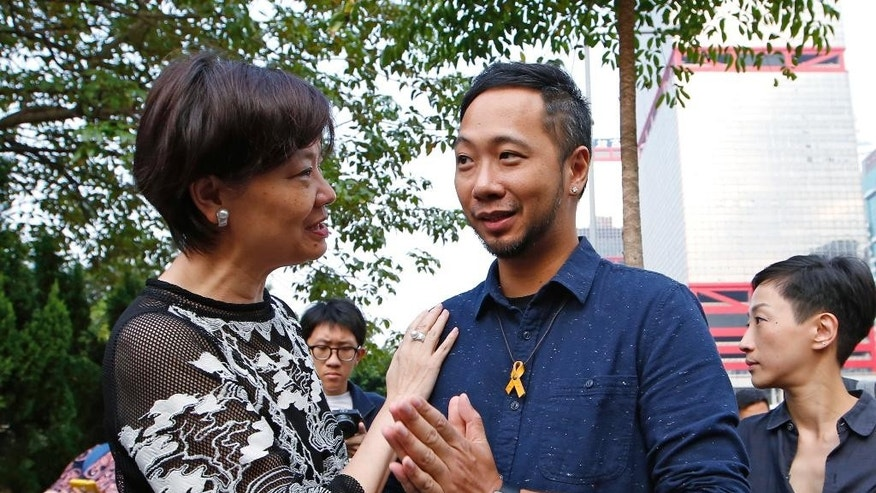 The activist, Ken Tsang, center, is greeted by his supporter Audrey Eu, chairman of the Civic Party, left, as he reports to a police station in Hong Kong, Thursday, Oct. 15, 2015. Hong Kong police on Thursday charged seven officers with harming an activist who was beaten in a filmed confrontation that stirred outrage among city residents at the height of the pro-democracy protests last year. (AP Photo/Kin Cheung)