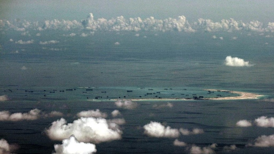 FILE - In this May 11, 2015, file photo, an aerial photo taken through a glass window of a military plane shows China's alleged on-going reclamation of Mischief Reef in the Spratly Islands in the South China Sea. As expectations grow that the U.S. Navy will directly challenge Beijing's South China Sea claims, China is engaging in some serious image-building for its own military by hosting two international security forums beginning Friday, Oct. 16, 2015. (Ritchie B. Tongo/Pool Photo via AP, File)
