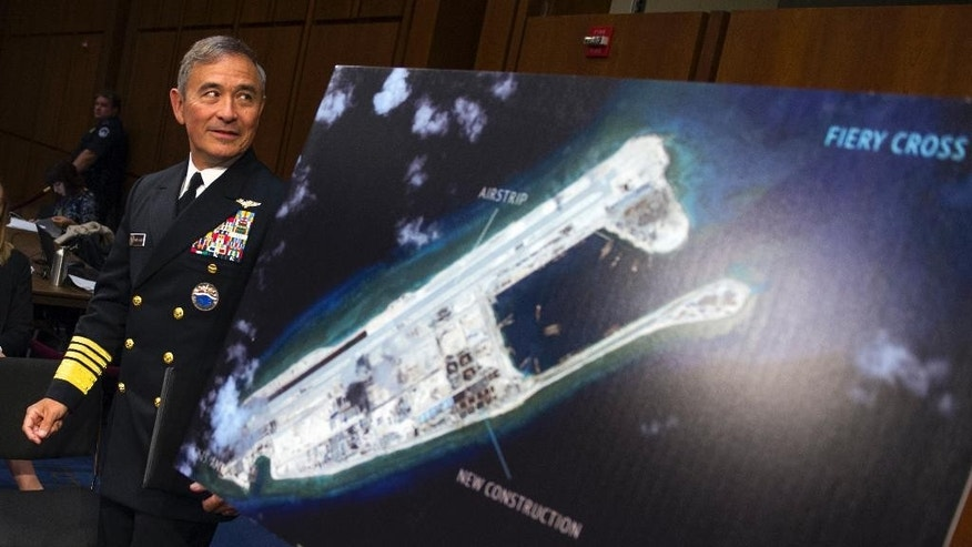 FILE - In this Sept. 17, 2015 file photo, Adm. Harry B. Harris, Jr. of U.S. Navy Commander, U.S. Pacific Command walks past a photograph showing an island that China is building on the Fiery Cross Reef in the South China Sea, as the prepares to testify on Capitol Hill in Washington. As expectations grow that the U.S. Navy will directly challenge Beijing's South China Sea claims, China is engaging in some serious image-building for its own military by hosting two international security forums beginning Friday, Oct. 16, 2015. (AP Photo/Cliff Owen, File)