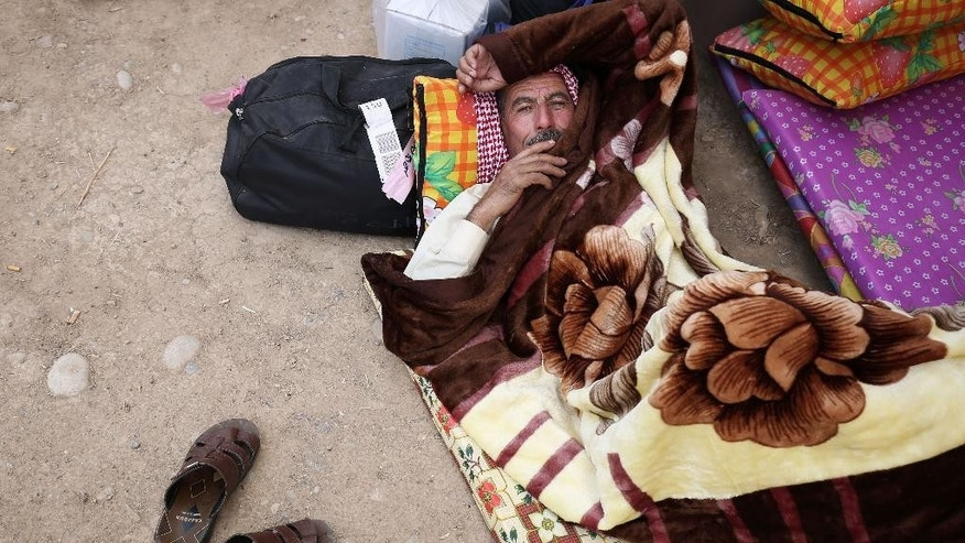 In this Wednesday, Oct. 14, 2015 photo, a man takes a rest underneath his blanket in the courtyard of a mosque in Kirkuk, Iraq along with over 500 elderly residents from Mosul are not allowed to return to the Islamic State held territory after returning from the annual hajj pilgrimage. The Iraqi government permitted only those above age 60 to exit militant territory, escorting them by bus to Baghdad, where they then flew to Mecca. But nearly two months later, the Mosuli hajjaj, as they are known in Arabic, are desperately trying to get home _ blocked by Iraqi and Kurdish authorities near the northern city of Kirkuk who refuse to open a corridor back into militant-held territory.(AP Photo/Bram Janssen)