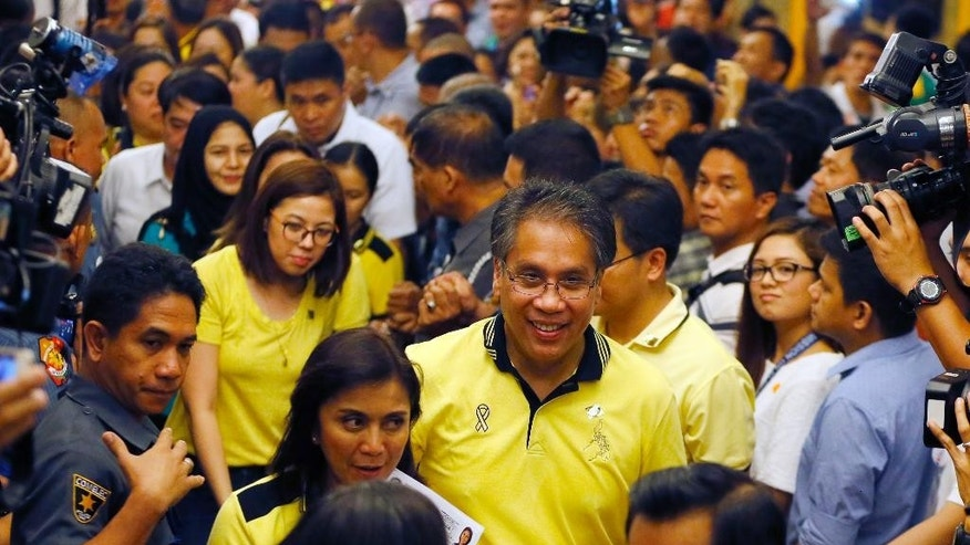 "Former Interior and Local Government Secretary and now a presidential candidate Mar Roxas,center, and running mate Maria Leonor ""Leni"" Robredo, second from left, hold their  respective certificates of candidacy shortly after filing before the Commission on Elections Thursday, Oct. 15, 2015 in Manila, Philippines. Roxas and Robredo are the standard-bearers of the ruling Liberal Party for next year's presidential elections. (AP Photo/Bullit Marquez)"