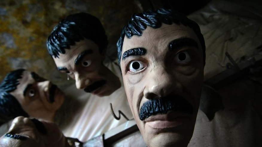"In this Tuesday, Oct. 13, 2015 photo, latex masks depicting Mexican drug lord Joaquin ""El Chapo"" Guzman, hang out to dry in the Caretas REV costume maker plant, in Cuernavaca, Mexico. The Mexican costume maker says prison jumpers and latex masks of the mustachioed, twice-escaped drug kingpin are selling like hotcakes. The company has produced more than 2,600 of the masks this month, many of them for export to the U.S. and Canada. (AP Photo/Tony Rivera)"