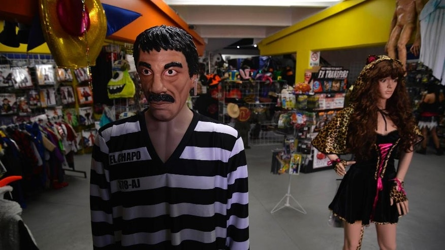 "In this Tuesday, Oct. 13, 2015 photo, a striped prison jumper and detailed latex mask representing the mustachioed, twice-escaped drug kingpin Joaquin ""El Chapo"" Guzman is displayed on a mannequin, in the showroom of costume maker Caretas REV, in Cuernavaca, Mexico. Costume designer Hector Bustos said the idea of producing a costume based on the drug lord began as a dark joke among colleagues but then they thought, Why not? Its popularity reflects the gallows-humor japes that many Mexicans told following ""El Chapo's"" second escape. (AP Photo/Tony Rivera)"