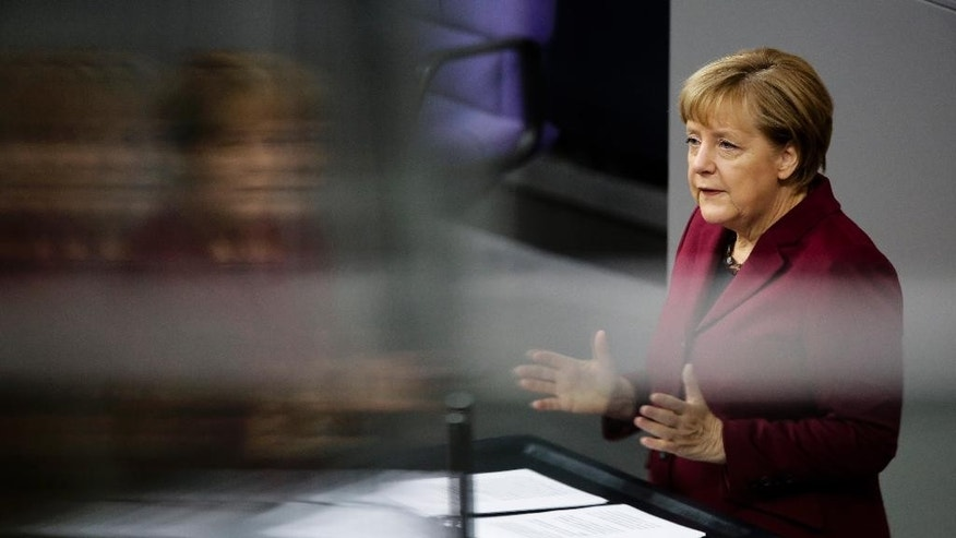 In this photo taken with a reflection in a window of the visitors tribune, German Chancellor Angela Merkel delivers a speech ahead of the EU summit in Brussels, at the German parliament Bundestag in Berlin, Germany, Thursday, Oct. 15, 2015. (AP Photo/Markus Schreiber)