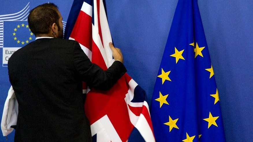 A member of protocol adjusts the British flag prior to a meeting of British Prime Minister David Cameron and European Commission President Jean-Claude Juncker at EU headquarters in Brussels on Thursday, Oct. 15, 2015. European Union heads of state meet Thursday to discuss, among other issues, the current migration crisis. (AP Photo/Virginia Mayo)