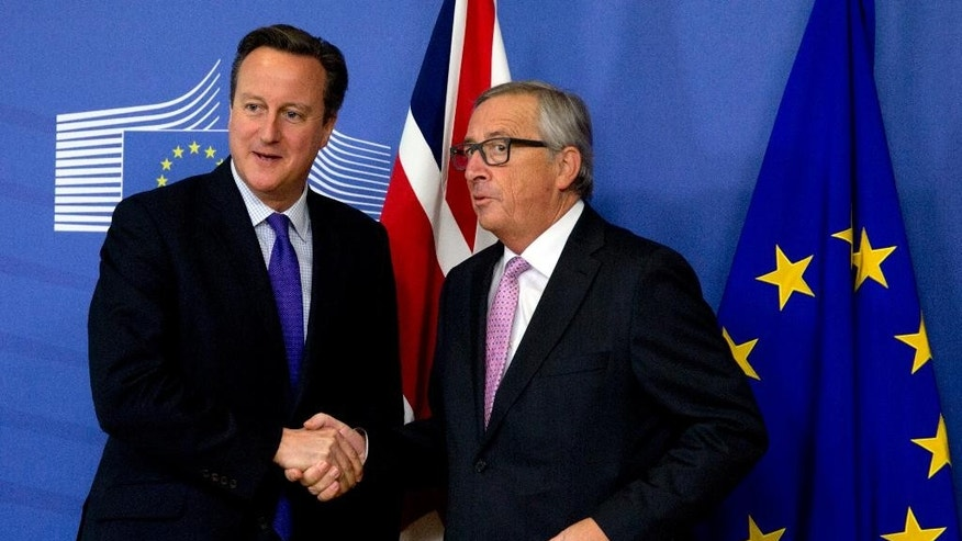 British Prime Minister David Cameron, left, is greeted by European Commission President Jean-Claude Juncker prior to a meeting at EU headquarters in Brussels on Thursday, Oct. 15, 2015. European Union heads of state meet Thursday to discuss, among other issues, the current migration crisis. (AP Photo/Virginia Mayo)