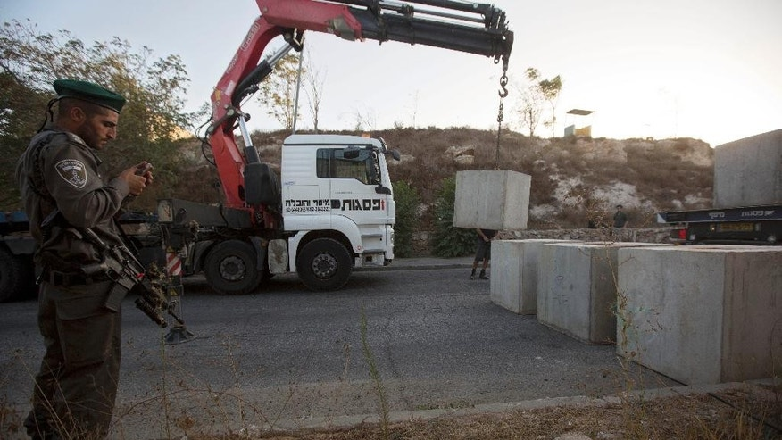 An Israeli border police officer stands guard as a worker places concrete blocks on the road at the entrance to the east Jerusalem neighborhood of Jabal Mukaber, Wednesday, Oct. 14, 2015.  The Israeli military began deploying hundreds of troops in cities across the country on Wednesday to assist police forces in countering a wave of deadly Palestinian shooting and stabbing attacks that have created panic across the country. (AP Photo/Sebastian Scheiner)