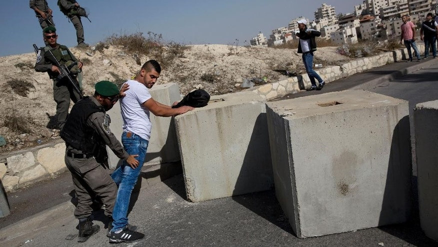Israeli border police search a Palestinian, next to newly placed concrete blocks in an east Jerusalem neighborhood, Thursday, Oct. 15, 2015. Israel erected checkpoints and deployed several hundred soldiers in the Palestinian areas of the city Wednesday as it stepped up security following a series of attacks in Jerusalem. (AP Photo/Oded Balilty)