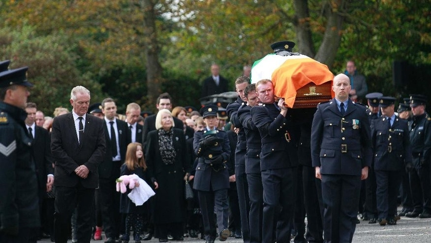 A guard of honour help carry the coffin of Irish police officer Tony Golden for his state funeral at St Oliver Plunkett Church, Blackrock, Ireland, Thursday, Oct. 15, 2015.  The police officer was gunned down Sunday as he responded to a domestic despite involving a dissident republican and his partner.  (AP Photo/Peter Morrison)