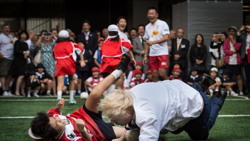 Mayor of London Boris Johnson knocks over 10 year-old Toki Sekiguchi who was unharmed in the collision, as Johnson participates in  Street Rugby tournament with school children and adults from Nihonbashi, Yaesu & Kyobashi Community Associations in Tokyo Thursday Oct. 15, 2015. Johnson is on the final day of his four day trade visit to Japan.   (Stefan Rousseau/PA via AP) UNITED KINGDOM OUT