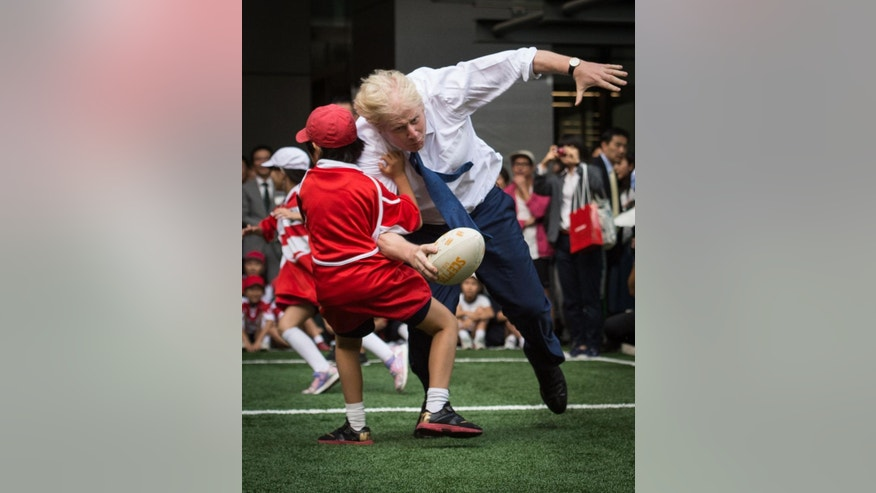 Mayor of London Boris Johnson knocks over 10 year-old Toki Sekiguchi who was unharmed in the collision as Johnson participates in a Street Rugby tournament with school children and adults from Nihonbashi, Yaesu & Kyobashi Community Associations in Tokyo Thursday Oct. 15, 2015. Johnson is on the final day of his four day trade visit to Japan.   (Stefan Rousseau/PA via AP) UNITED KINGDOM OUT