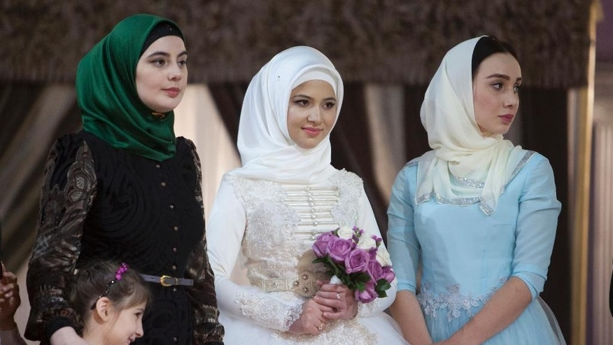 In this Wednesday, Oct. 14, 2015, photo, a Chechen bride dressed in national costume is surrounded by her relatives, as she waits for her wedding ceremony to begin in Grozny, Russia. Chechen weddings are traditionally paid for by the groom and attended by his family members. (AP Photo/Musa Sadulayev)