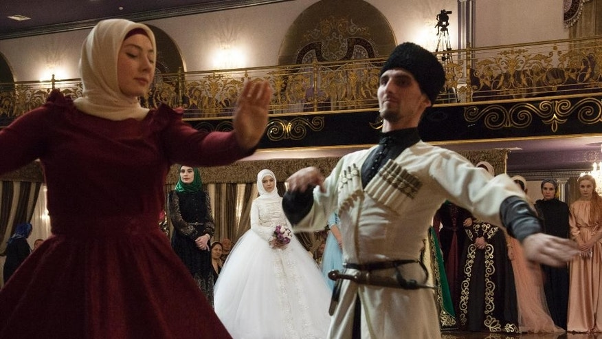 In this photo taken on Wednesday, Oct.  14, 2015,  a Chechen couple dressed in national costumes dance in front of a bride during a wedding ceremony in Grozny, Russia. Chechen weddings are traditionally paid for by the groom and attended by his family members. (AP Photo/Musa Sadulayev)