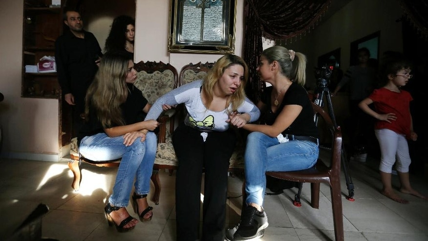 Relatives of the Safwan family mourn at the family house in Beirut's southern suburb of Ouzai, Lebanon, Thursday, Oct. 15, 2015 after a rubber boat carrying a family of 12 of their relatives to European shores sunk, drowning five while four are still missing. The Lebanese family tragedy highlights how the flood of refugees is encouraging more disenchanted around the region to take the journey to Europe, expected to get riskier in winter. (AP Photo/Hassan Ammar)