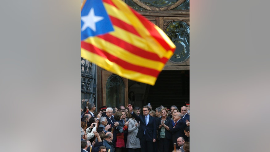 Regional acting President Artur Mas, center, waves to the crowd as he leaves Catalonia's high court after being questioned over their suspected roll in holding a poll in Barcelona, Spain, Thursday, Oct. 15, 2015. Thousands of people are rallying outside a Barcelona court in support of Catalan regional acting President Artur Mas who has arrived for questioning over the staging of a symbolic referendum on secession from Spain last year. (AP Photo/Manu Fernandez)