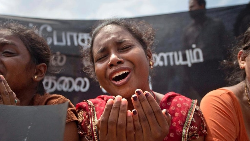 FILE - In this Wednesday, Oct. 14, 2015 file photo, a family member of an ethnic Tamil detainee cries during a silent protest in Colombo, Sri Lanka. Sri Lanka's government has pledged to quickly process hundreds of ethnic Tamils who have been detained without charges for years on suspicion of links to former Tamil Tiger rebels. (AP Photo/Eranga Jayawardena, File)