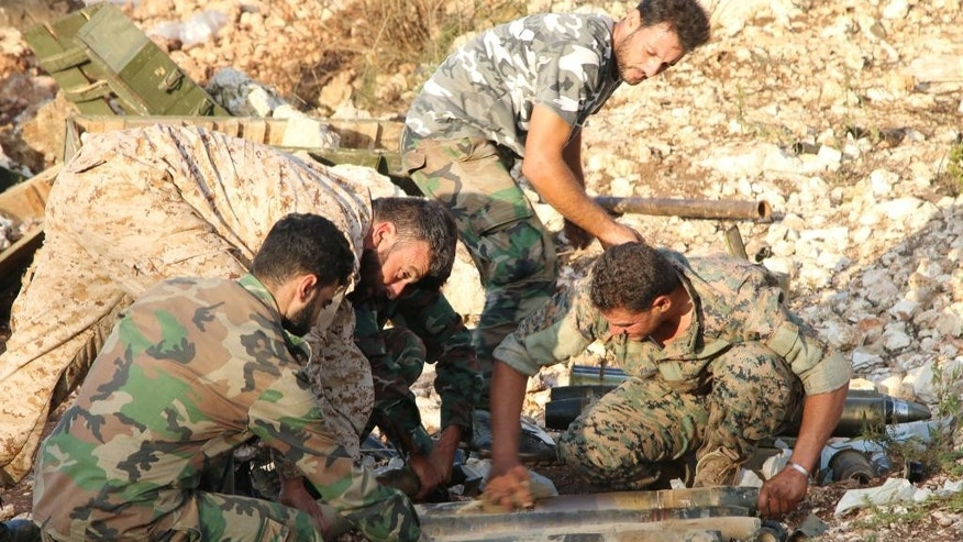 In this photo taken on Saturday, Oct. 10, 2015, Syrian army personnel prepare artillery ammunition in Latakia province, about 12 miles from the border with Turkey, Syria. Backed by Russian airstrikes, the Syrian army has launched an offensive in central and northwestern regions.  (Alexander Kots/Komsomolskaya Pravda via AP)