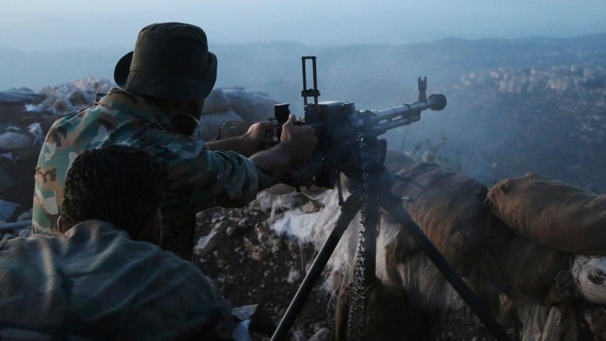 In this photo taken on Saturday, Oct. 10, 2015, Syrian army personnel fire a machine gun in Latakia province, about 12 miles from the border with Turkey, Syria. Backed by Russian airstrikes, the Syrian army has launched an offensive in central and northwestern regions.  (Alexander Kots/Komsomolskaya Pravda via AP)