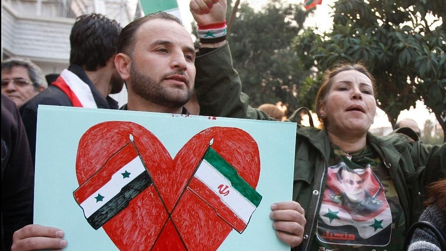 """FILE - In this November 24, 2011 file photo, a pro-Syrian regime protester holds a placard showing the Iranian and Syrian flags with Arabic words reading: """"Thanks Iran,"""" during a protest in front the Iranian embassy to thank Iran for their support of the Syrian regime, in Damascus, Syria. Hundreds of Iranian troops are being deployed in northern and central Syria, dramatically escalating Tehran's involvement in the civil war as they join allied Hezbollah fighters in an ambitious offensive to wrest key areas from rebels amid Russian airstrikes. (AP Photo/Muzaffar Salman, File)"""