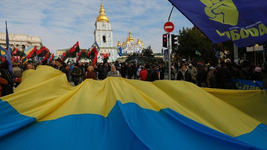 Activists of the nationalist Svoboda (Freedom) party and activists of the Right Sector hold flags during a rally in Kiev, Ukraine, Wednesday Oct. 14, 2015. Ukraine is marking Defender of the Fatherland Day. (AP Photo/Sergei Chuzavkov)