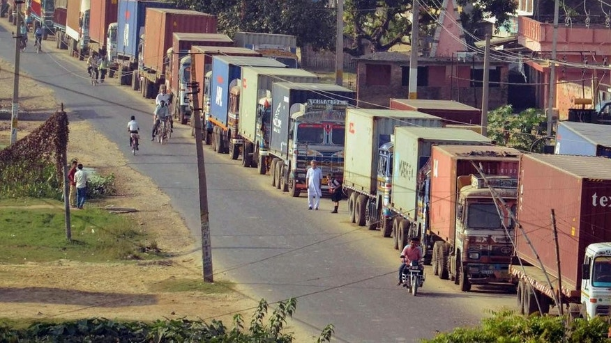 In this Wednesday, Oct. 14, 2015 photo, trucks stand stranded at Birganj, a town on the border with India, Nepal. Hundreds of ethnic Madhesis are protesting against Nepal's new constitution. With them blocking the road, many parked cargo trucks stretches at least 18 miles (30 kilometers) from the Nepalese border. Some have been waiting on the Indian side for 45 days. (AP Photo/Aftab Alam Siddiqui)