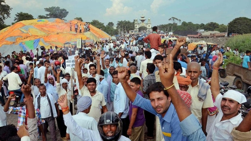 In this Wednesday, Oct. 14, 2015 photo, activists of Nepal's Madhesi group protest against the new constitution at Birganj, a town on the border with India, Nepal. Nepal has accused India of imposing an economic blockade to support the protesting Madhesis, who have strong links with India, in their demand for more constitutional representation. The border impasse _ now in its third week _ has halted the majority of shipments into Nepal and left the Himalayan nation hobbled by a shortage of fuel and goods. (AP Photo/Aftab Alam Siddiqui)