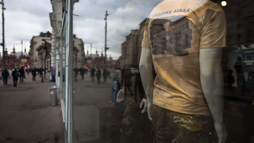 A mannequin seen through a glass window displays a T-shirt with a picture of a target hit by Russian air strike in Syria and words 'Support Assad', at the Russian Army Store in downtown Moscow, near the Kremlin, Russia, Thursday, Oct. 15, 2015, with the Historical museum is in the background. The Army Store has put on sale new products emblazoned with images of Russian air raids in Syria which began on Wednesday, Sept. 30, 2015. (AP Photo/Alexander Zemlianichenko)