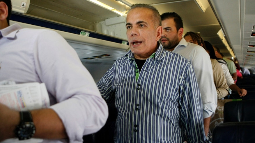 Venezuelan opposition leader Manuel Rosales, center, stand as he waits to leave a plane after it landed at La Chinita airport in Maracaibo, Venezuela, Thursday, Oct. 15, 2015. Rosales a former governor, who had been living in exile since 2009, was arrested when he returned to Venezuela and is expected to appear in a Caracas court later in the day. Rosales ran for president in 2006 and lost to Hugo Chavez. (AP Photo/Jhair Torres)