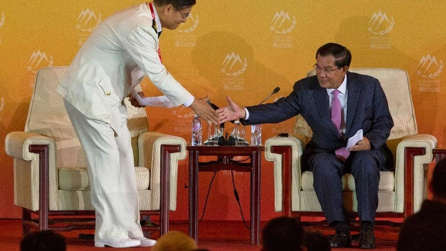 Admiral Sun Jianguo, Chairman of China Institute for International Strategic Studies, left, shakes hands with Cambodia Prime Minister Hun Sen after speaking at the welcome banquet of the 6th Xiangshan Forum at which analysts, military leaders and others from around the globe will discuss Asian-Pacific security, maritime issues and anti-terrorism in Beijing, Friday, Oct. 16, 2015. China vastly expanded the scope of the Xiangshan Forum last year, making it an annual rather than biennial event and boosting participation to more than 300 defense officials and academics from 47 countries. (AP Photo/Ng Han Guan)