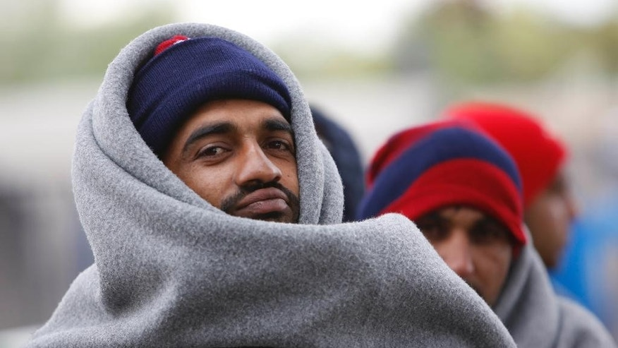 Migrants wrapped in blankets wait to board busses that will take them to Hungary from the admission center in Opatovac, Croatia, on Thursday, Oct.15, 2015. The migrants and refugees are struggling with the autumn rain and the cold as EU leaders are discussing in Brussels how to deal with the crisis. (AP Photo/Amel Emric)
