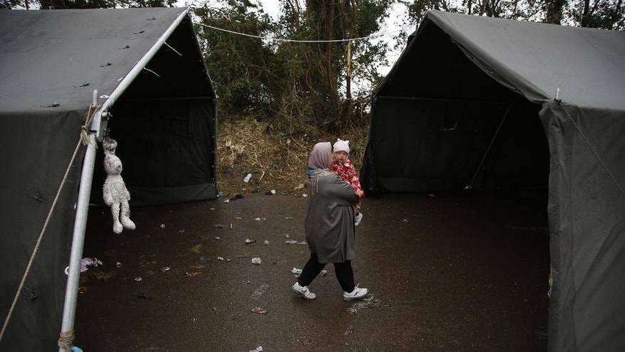 A woman carries her child over the Serbian-Croatian border in the village of Berkasovo, near Sid, Serbia, on Thursday, Oct. 15, 2015. The migrants and refugees are struggling with the autumn rain and the cold as EU leaders are discussing in Brussels how to deal with the crisis. (AP Photo/Amel Emric)